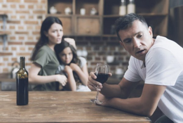 man-drinking-wine-with-sad-family-in-background-522x350